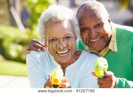 Senior Couple Shooting Water Pistols