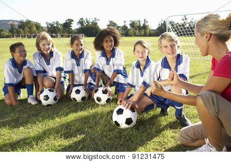 Group Of Children In Soccer Team Having Training With Female Coach poster