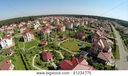 Aerial view gated development near forest at sunny summer day.