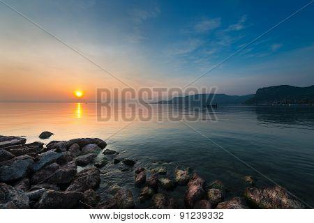 moody sunset at lake gardasee with rocks at coast