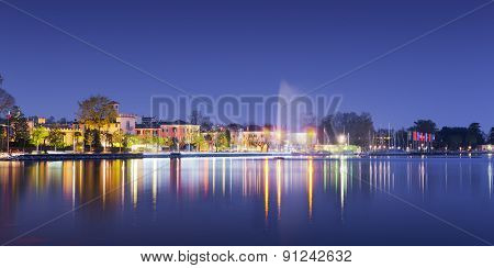 beach of city bardolino with reflections in lake at night