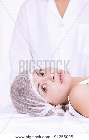 Young girl lying down ready to get a cosmetic treatment