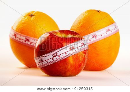 Oranges And Apple With Tailor's Ruler. Fruit Healhy Vitamin Diet Helps To Lose Weight.