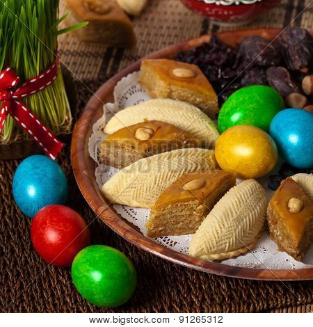 Novruz in Azerbaijan. Colored eggs for easter and traditional sweets. Selective focus. poster