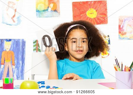African girl holds flashcard with zero at  desk