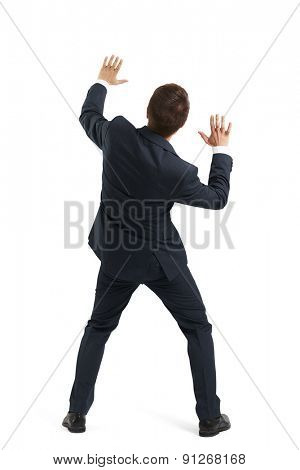 back view of startled businessman in formal wear moving aside and covering hands. isolated on white background