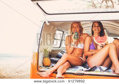 Surfer Girls Beach Lifestyle, Friends Hanging out Eating Watermelon in the Back of Classic Vintage Surf Van on the Beach at Sunset