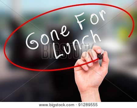 Man Hand writing Gone For Lunch with marker on transparent wipe board.