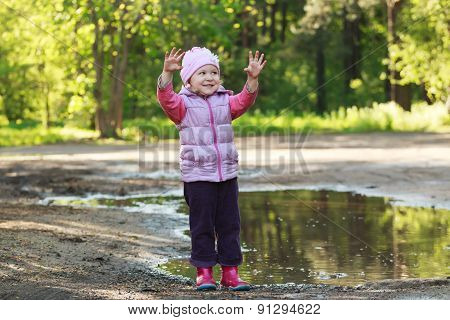 Smiling tree years old girl standing in summer puddle and showing her dirty palms