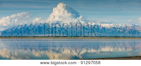 Wasatch Mountain Range Utah Snow capped clouds reflecting in Salt Lake blue sky panoramic pano
