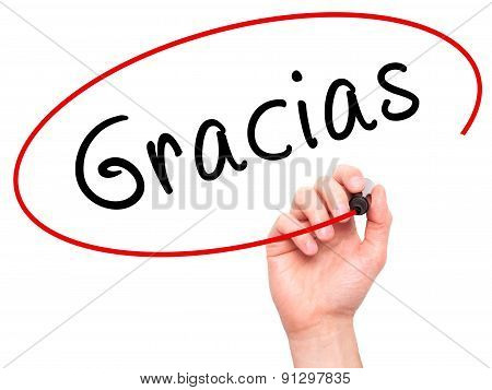 Man Hand writing Gracias with marker on transparent wipe board.