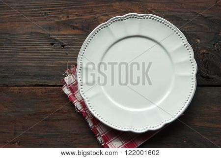 Empty plate and napkin on a wooden background of a table. Top view