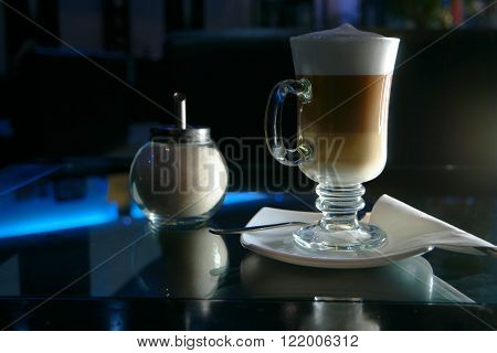 Glass of latte coffee shugar and spoon on modern glass table.