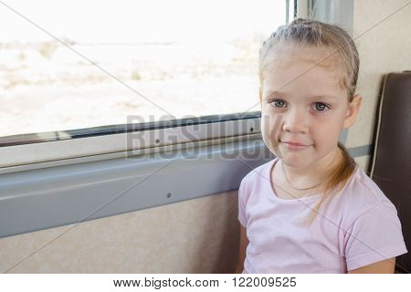 Happy Girl Sitting On A Chair By The Window In A Suburban Electric Train