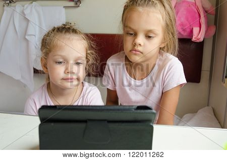 Sisters Looking At Tablet In The Train