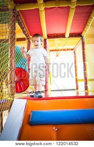 Little kid climbing on stairs in kindergarden playground