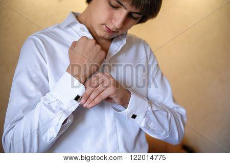 groom wears cuff links on white shirt.