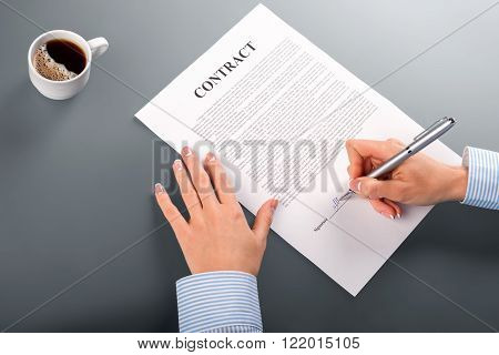 Female hands sign contract. Close-up of businesswoman signing contract. Morning coffee and paperwork. Finally a smart decision.