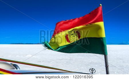 Salt Flats, Bolivia - August 08, 2015: Bolivia national flag flying in the wind over a car in the salt flats desert in South America