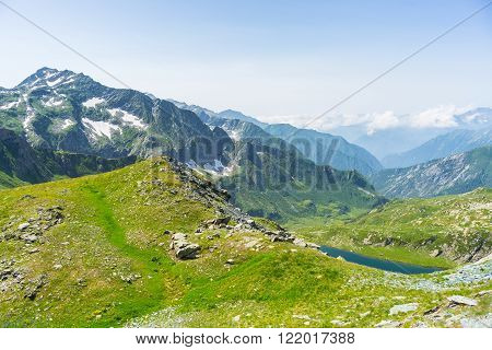 High altitude blue lake in idyllic uncontaminated environment once covered by glaciers. Summer season in Gran Paradiso National Park, Italian Alps. Wide angle view from above.