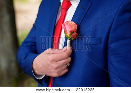 a buttonhole holds the suit of fiance a hand