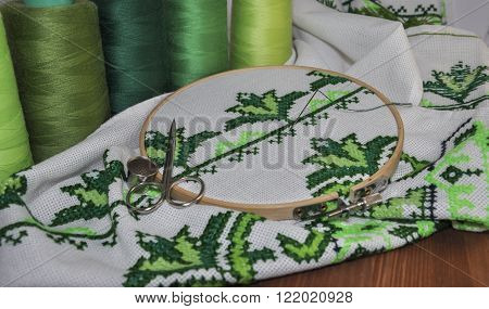 Close-up of embroidery needle and thread and embroidery products with green thread