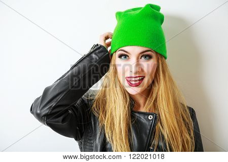 Portrait of Beautiful Street Style Hipster Girl in Beanie Hat Going Crazy on White Background. Not Isolated Photo with Shadow. Trendy Casual Fashion Outfit in Spring or Autumn. Copy Space.