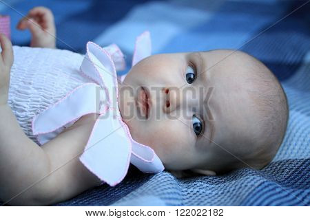 Baby Girl In A Dress With Ribbons Lying On A Coverlet