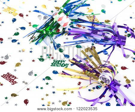 Colorful birthday decoration of noisemakers and confetti on a white background