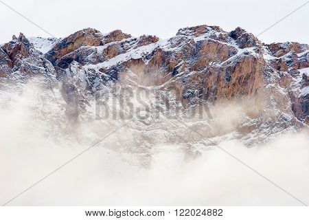 A steep wall of rock rises from the clouds in the Brooks Range, Alaska