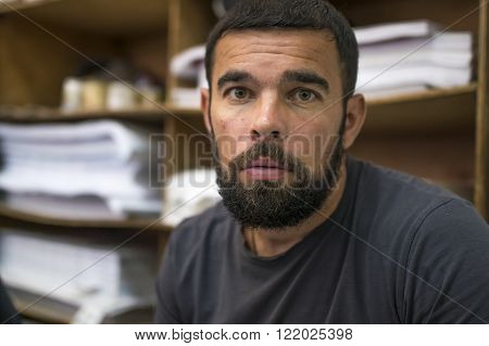 Portrait of surprised bearded middle-aged man on the background of stillage