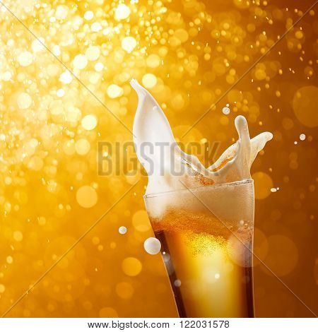 glass of splashing beer against golden bokeh background
