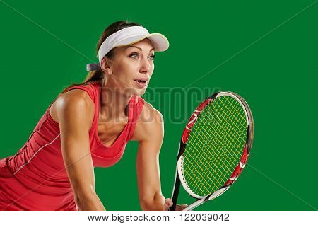 Woman playing tennis and waiting for the service. in a green screen studio.Young woman with copy space on green screen chroma key
