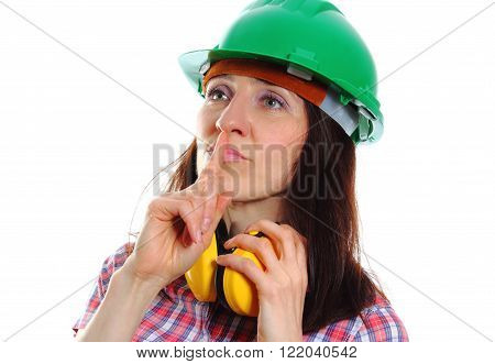 Female construction worker wearing green helmet and protective headphones, holding finger to lips and showing silence sign, safety at work and ear protection. White background