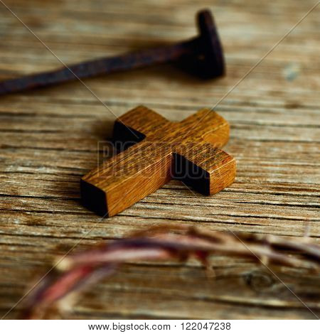 closeup of a small wooden cross, a depiction of the crown of thorns of Jesus Christ and a nail on a wooden surface