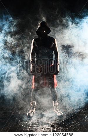 The young male athlete kickboxing standing on a background of blue smoke ** Note: Visible grain at 100%, best at smaller sizes