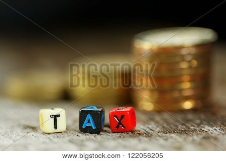 Tax concept with TAX word on alphabet block with stacked coin in the background