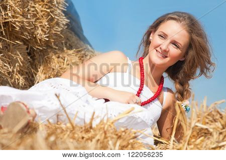 Young smiling beautiful young woman in a white sundress on a haystack in the summer on a bright sunny day