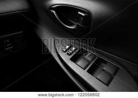 Car interior details of door handle with windows controls and adjustments. Car window controls and details poster