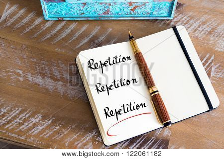 Retro effect and toned image of a fountain pen on a notebook. Handwritten text Repetition Repetition Repetition as business concept image poster