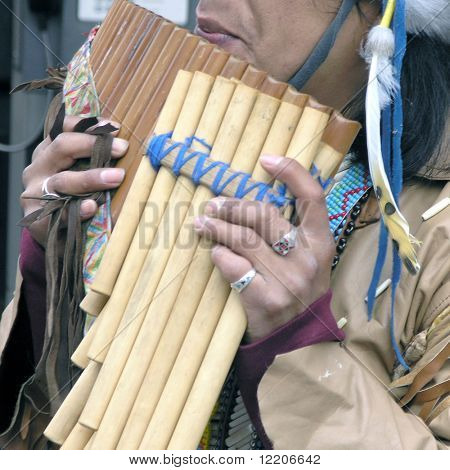 Musician in native american dress playing pipes.