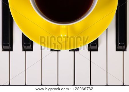 Detail of piano keyboard and cup of coffee