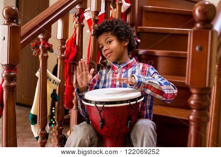 Young afro drummer on stairs. Playing djembe like a pro.