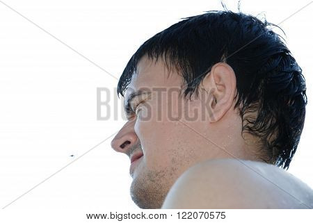 On a white background a man with wet hair squinting looking at insect