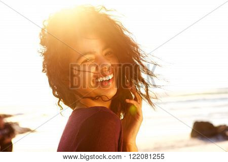 Carefree Young Woman With Curly Hair Laughing Outdoors