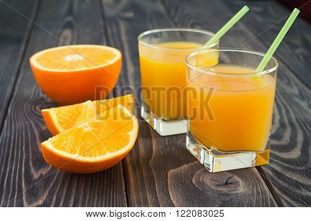 Fresh orange juice in the glasses with tubule with orange havel on a brown wooben table. Selective focus