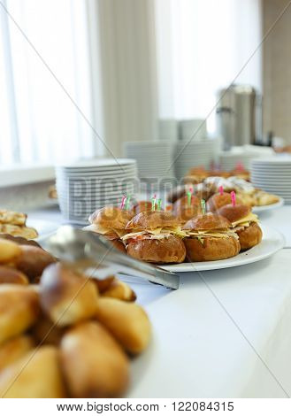 Selective focus photo catering banquet table with baked food snacks sandwiches cakes and plates self serve open buffet dinner