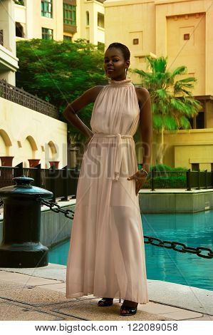 African woman in a luxury dress near pool area