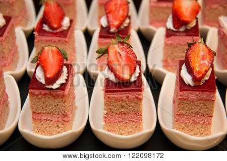 A peice of strawberry cake as closeup on a white cup