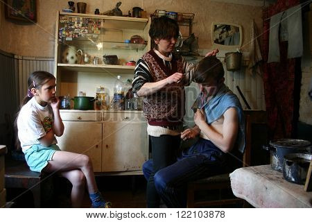Lipovec village Tver region Russia - May 7 2006: Family Russian farmers in his home Kitchen in peasant house his mother makes her son a haircut.